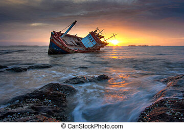 shipwreck stranded on the beach at sunset
