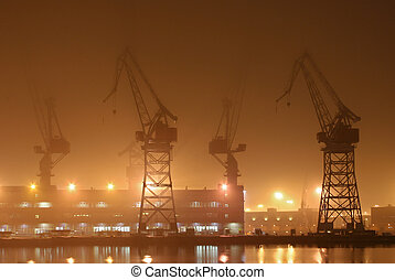 Cranes in thick fog in Helsinki shipyard