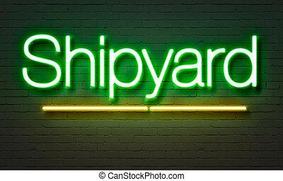 Shipyard neon sign on brick wall background.