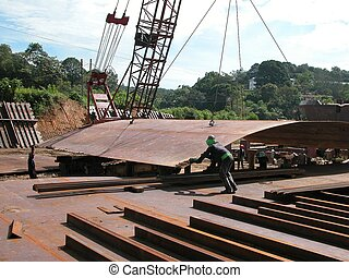 Workers unloading steel plates in a Malaysian shipyard. Shipbuilding is one of the major industries in Sarawak, East Malaysia