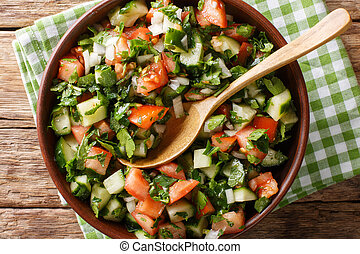 Shirazi salad of cucumbers, tomatoes, onions and herbs close-up in a bowl. Horizontal top view