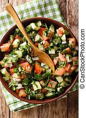 Shirazi salad of cucumbers, tomatoes, onions and herbs close-up in a bowl. Vertical top view