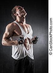 Shirt off - Brutal athletic man rips shirt on dark ...