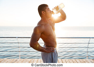 Shirtless african muscular young man drinking water on pier
