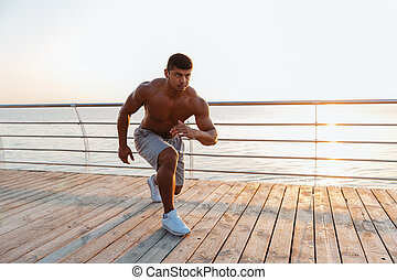 Shirtless african young sportsman working out on pier