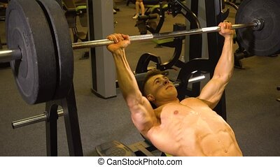 Shirtless athlete exercising with barbell - Muscular young...