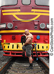 shirtless athlete stands on railroad against locomotive