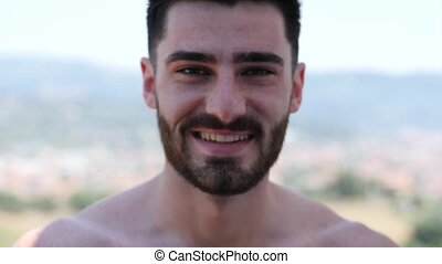 Shirtless athletic man smiling to camera