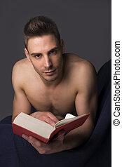 Shirtless athletic young man reading big book