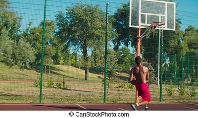 Shirtless muscular build african basketball player recieving pass from teammate, driving to hoop, jumping in the air and performing slam dunk with one hand while playing streetball game at urban court