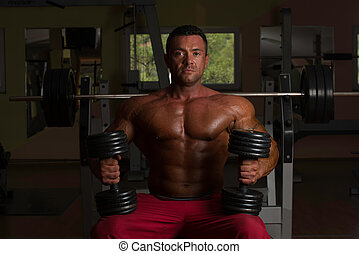 shirtless body builder posing with dumbbell at the bench