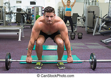 Shirtless bodybuilder about to lift heavy barbell