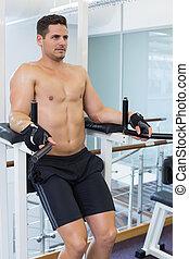 Shirtless bodybuilder doing leg lifts