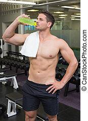 Shirtless bodybuilder drinking sports drink