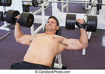 Shirtless bodybuilder lifting heavy dumbbells lying on bench