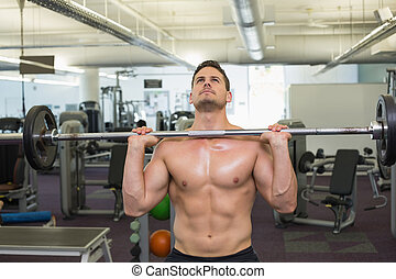 Shirtless bodybuilder lifting heavy barbell weight