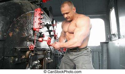 shirtless bodybuilder opening furnace in locomotive