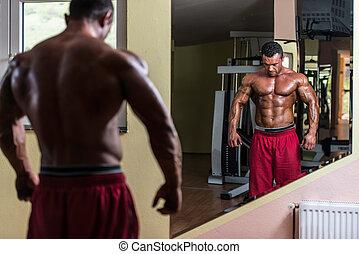 shirtless bodybuilder posing at the mirror