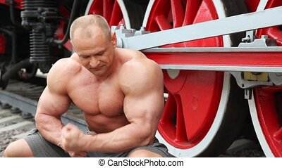shirtless bodybuilder seat on railroad against locomotive