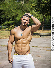Shirtless bodybuilder showing torso muscles, abs, pecs and...