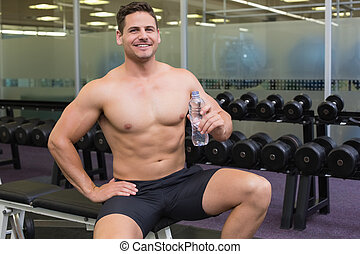 Shirtless bodybuilder sitting on bench with water bottle