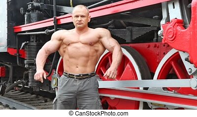 shirtless bodybuilder stands on railroad against locomotive