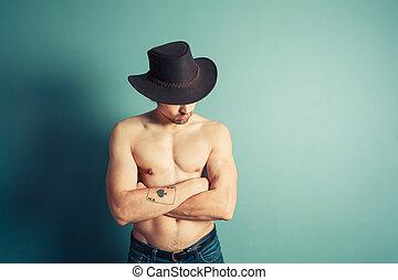Shirtless cowboy striking a pose by blue wall
