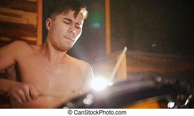 Shirtless drummer plays music in studio