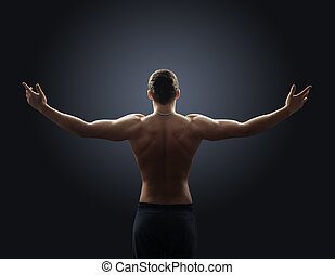 shirtless guy spreads his arms out to the side back