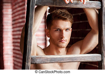 Shirtless handsome. Close-up of handsome young shirtless man leaning at the wooden ladder and looking at camera while standing near the brick wall