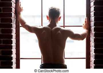 Shirtless handsome. Rear view of young shirtless man looking...