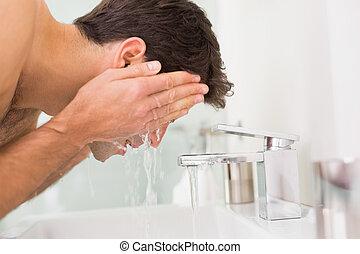 shirtless, joven, cara que se lava, en, cuarto de baño