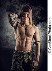 Shirtless male model wearing a bandanna smiling on smoky...