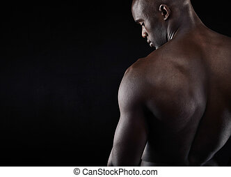 Shirtless male model with copyspace - Rear view of young man...