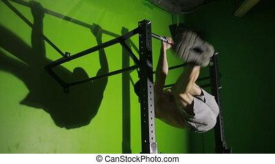 Shirtless man doing stomach exercises on a horizontal bar....