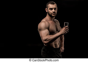 shirtless man holding glass of water in hand isolated on black