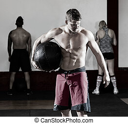 Shirtless Man Holding Medicine Ball In Gym