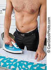 Shirtless Man Ironing Shirt On Table