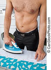 Shirtless Man Ironing Shirt On Table