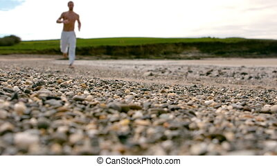Shirtless man jogging by the coast