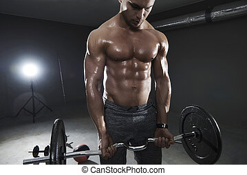 Shirtless man lifting heavy weights