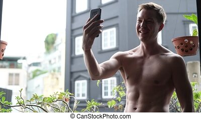 Shirtless Man Outdoors In Balcony Taking Selfie And Vlogging With Mobile Phone