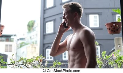 Shirtless Man Outdoors In Balcony Talking On Mobile Phone