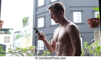 Shirtless Man Outdoors In Balcony Using Mobile Phone
