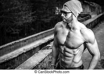 Stylish muscle man posing topless outdoor in urban fashion manner