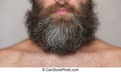 Shirtless man shaving with electric razor