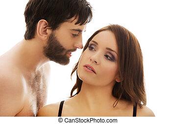 Shirtless man whispering to woman's ear.