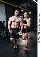 shirtless man with water bottle posing with sportive woman near by