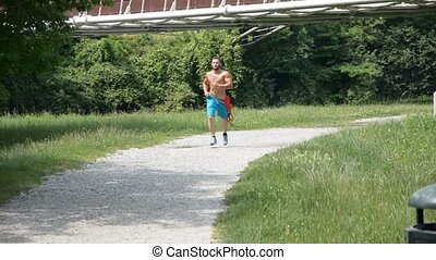 Shirtless muscle man jogging on pathway