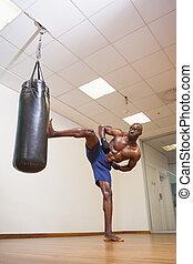 Shirtless muscular boxer kicking pu